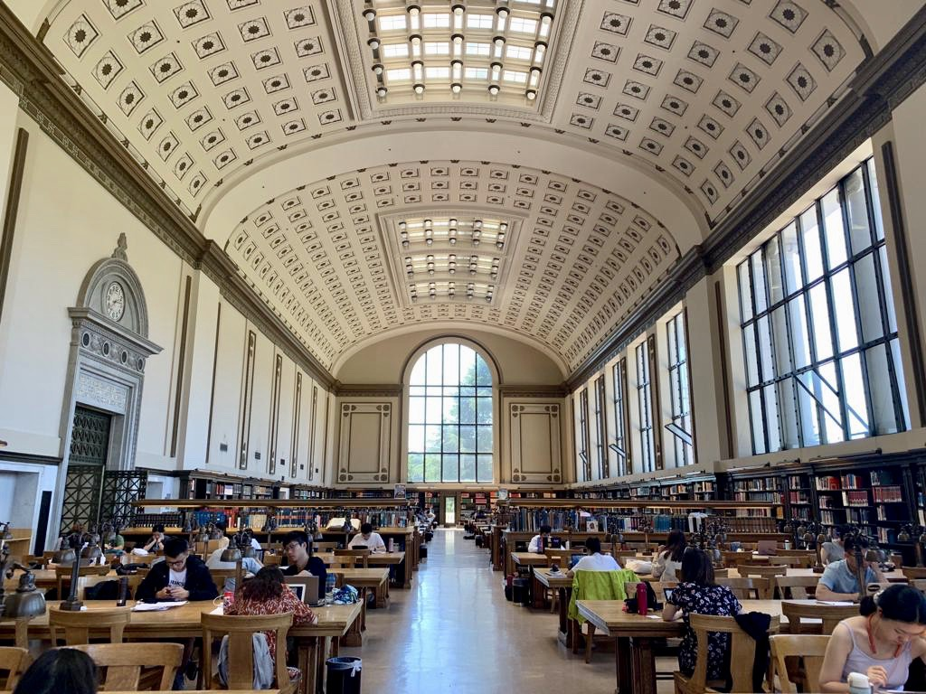 Inside look of UC Berkeley library with students studying at tables