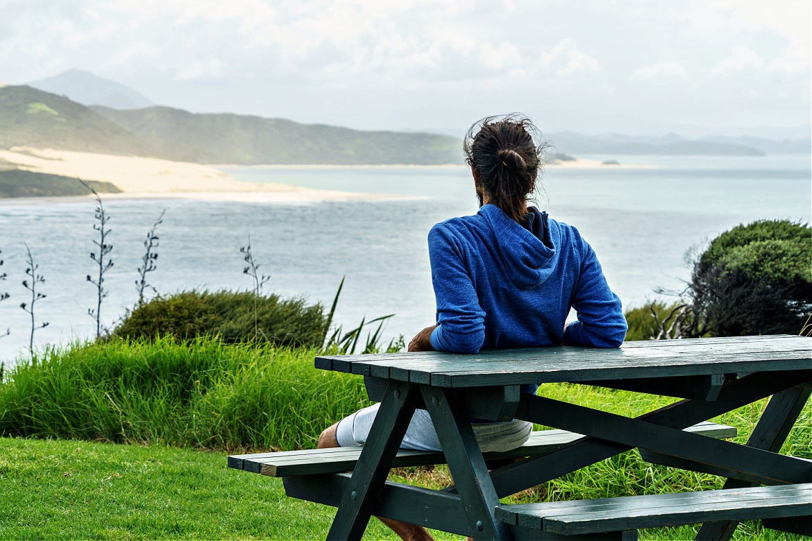 Man sitting at picnic table with his back to us looking out at the ocean