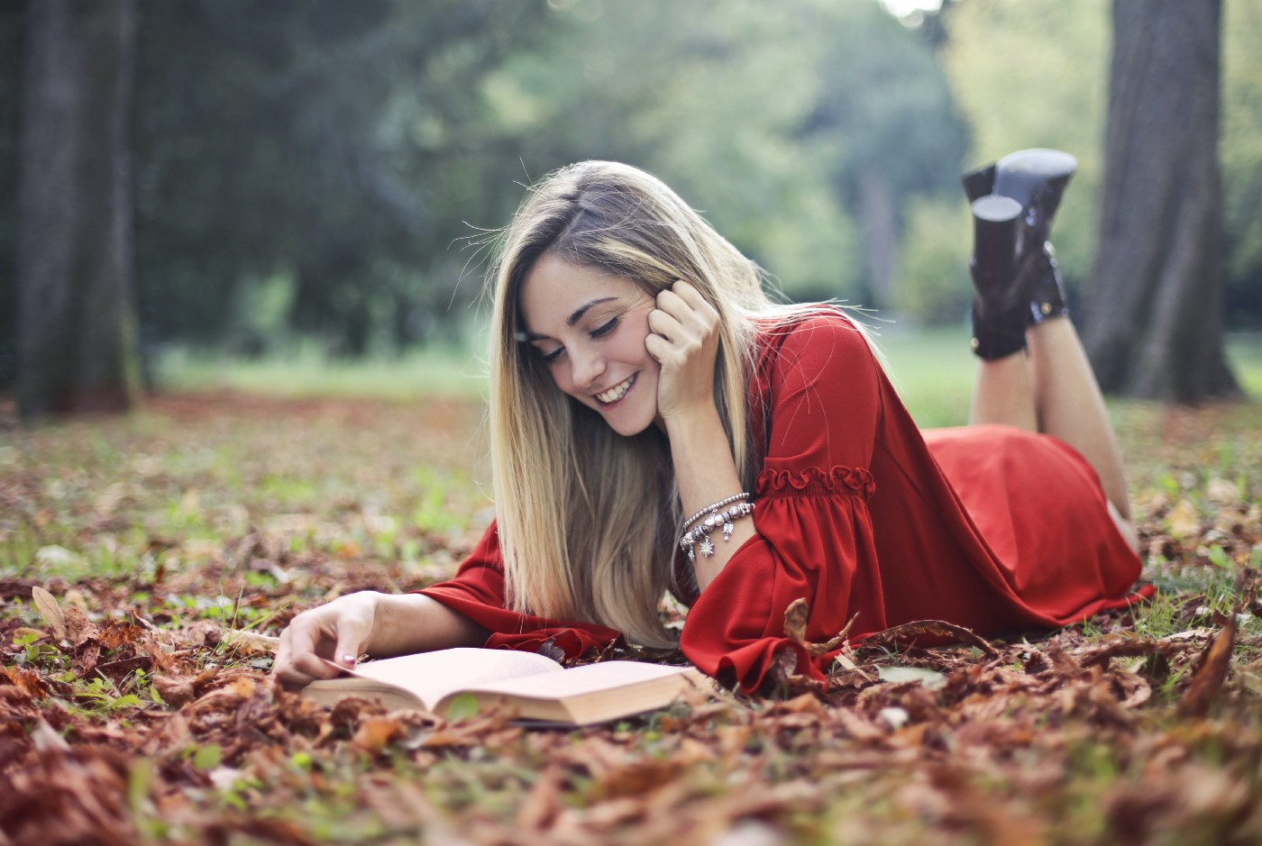Girl reading a book in the leaves