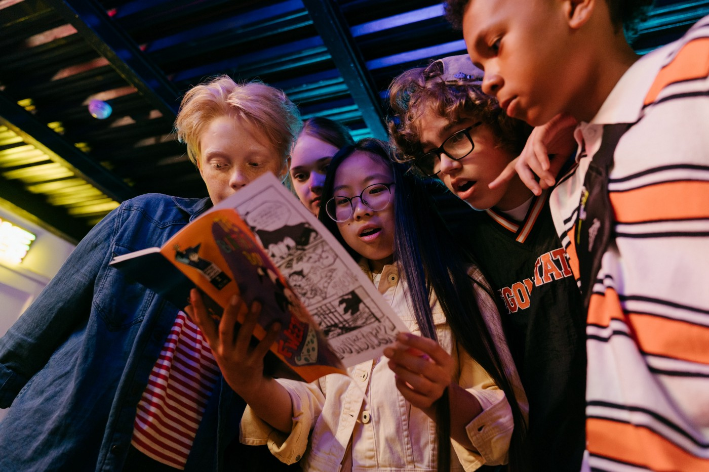 Five children reading a comic book together