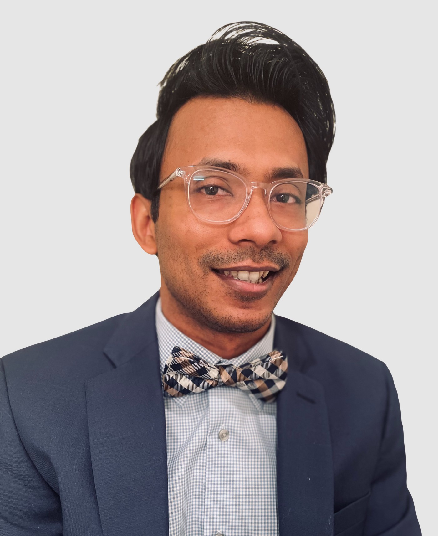Headshot of Ather, who is Asian, smiling, wearing a navy suit and checkered bowtie. He is wearing thick clear-framed glasses.