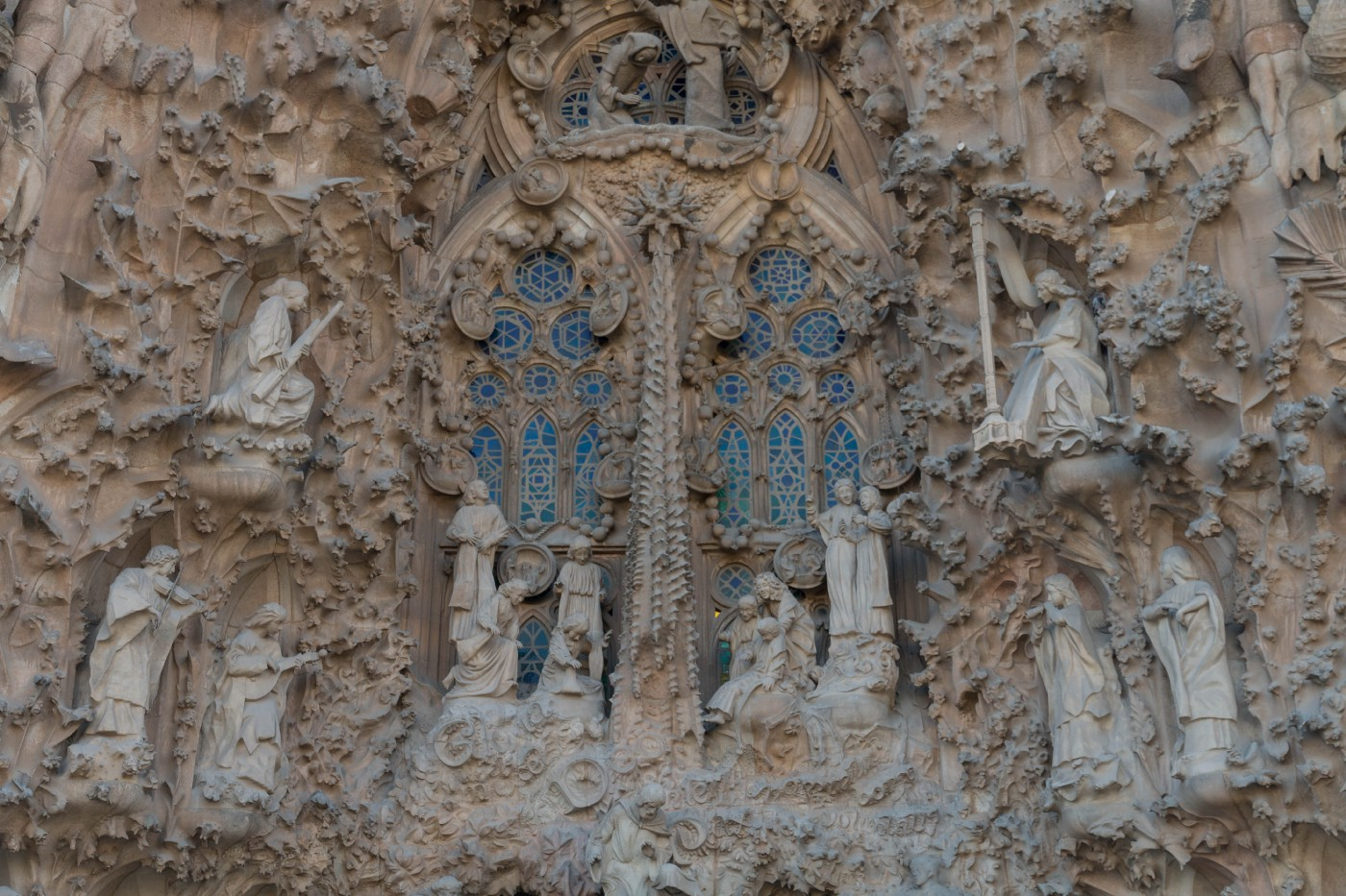 Sculptures of people surround blue tinted windows on the outside of the Sagrada Família.