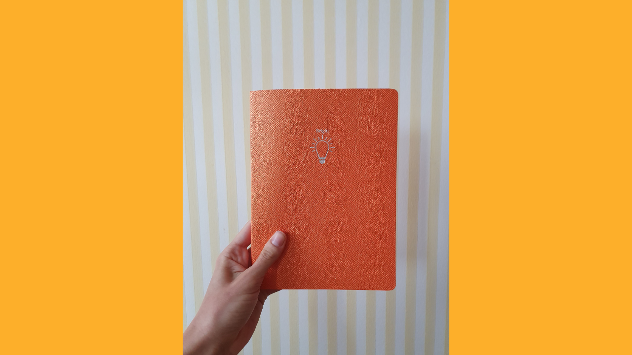 """image of an orange journal with the word """"bright"""" and a lightbulb icon against a yellow-and-white striped wall."""