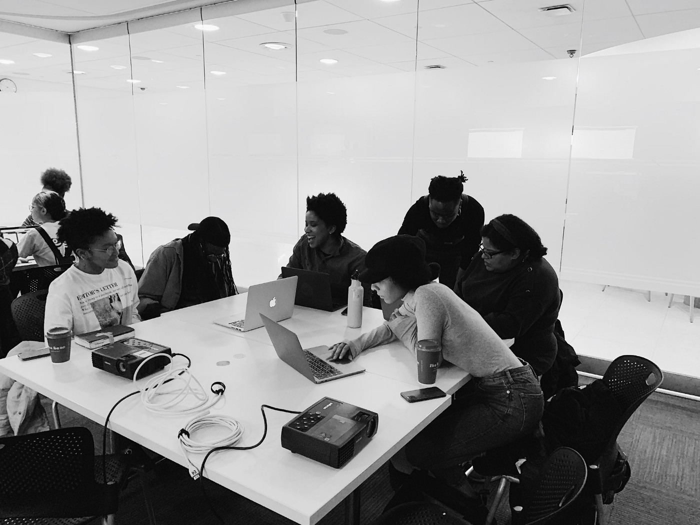 Black and white photo of seven people gathered around a table with laptops.