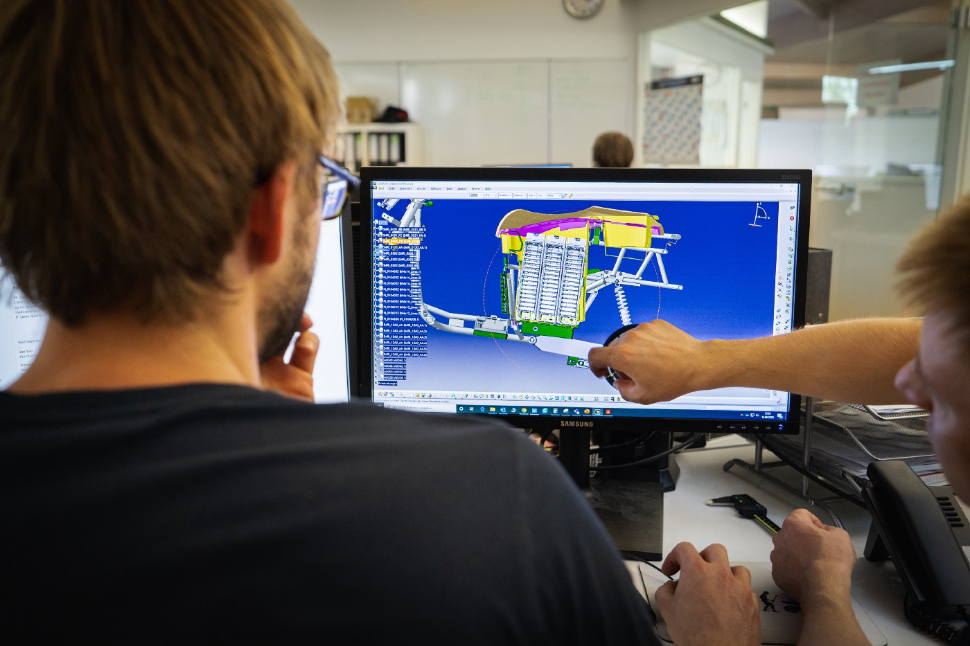 Engineers at an electric car company design the back hood on a computer.