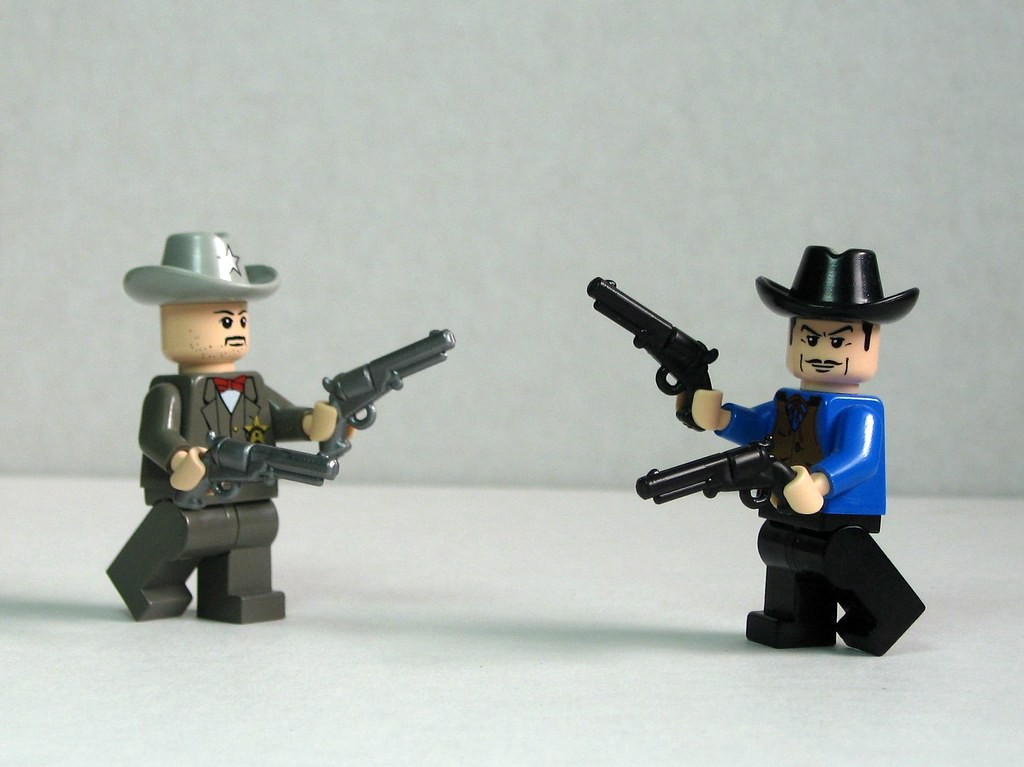 A photo of two Lego characters. They are wearing old wild west costumes and holding two toy guns each.