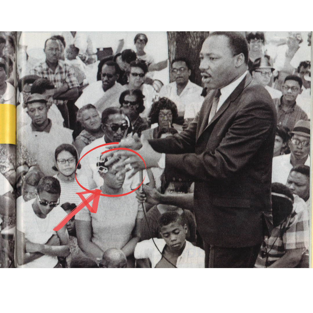 Black and white photo of Martin Luther King speaking to a crowd of Black people in Cleveland, Ohio. A woman in the front wearing rollers in her hair is circled in red. A red arrow points to her.