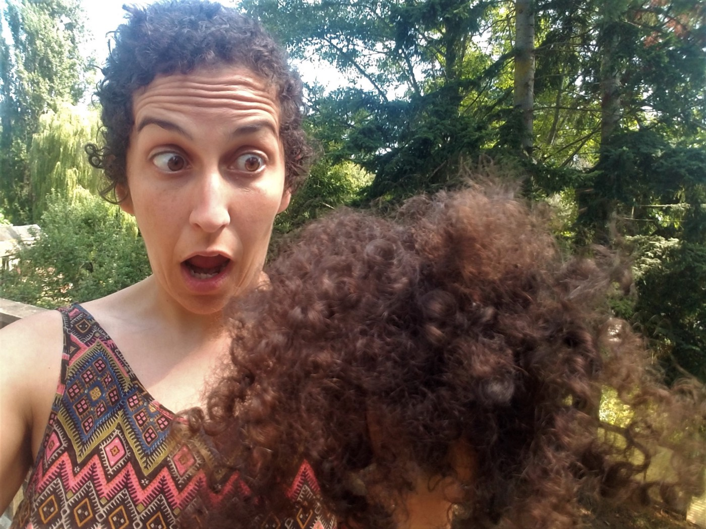Author with short hair making a funny shocked face looking at her cut-off brown curly hair.