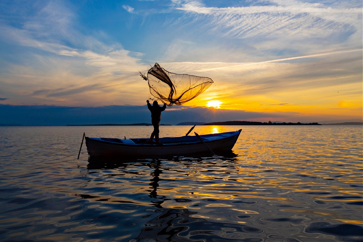 Man in a boat throwing out a fishing net at sunrise.