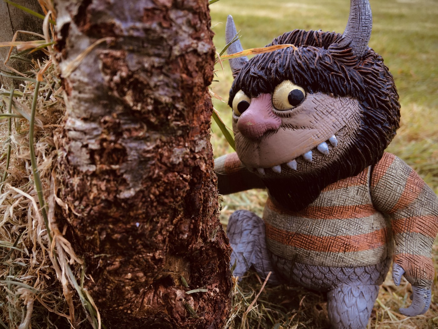 One of Maurice Sendak's Wild Things, watching us by a tree.