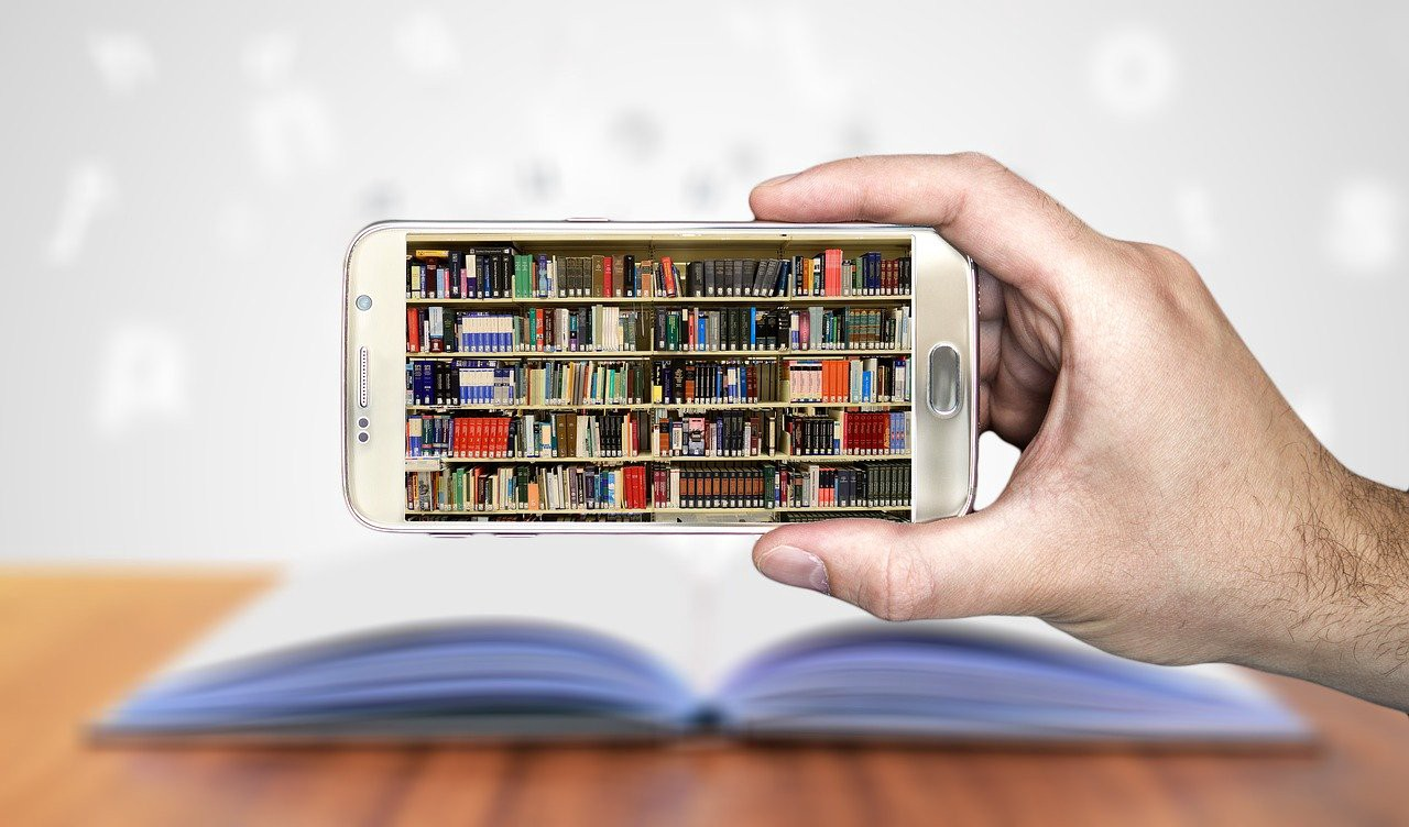 Hand holding a cell phone with shelves of books in the screen.