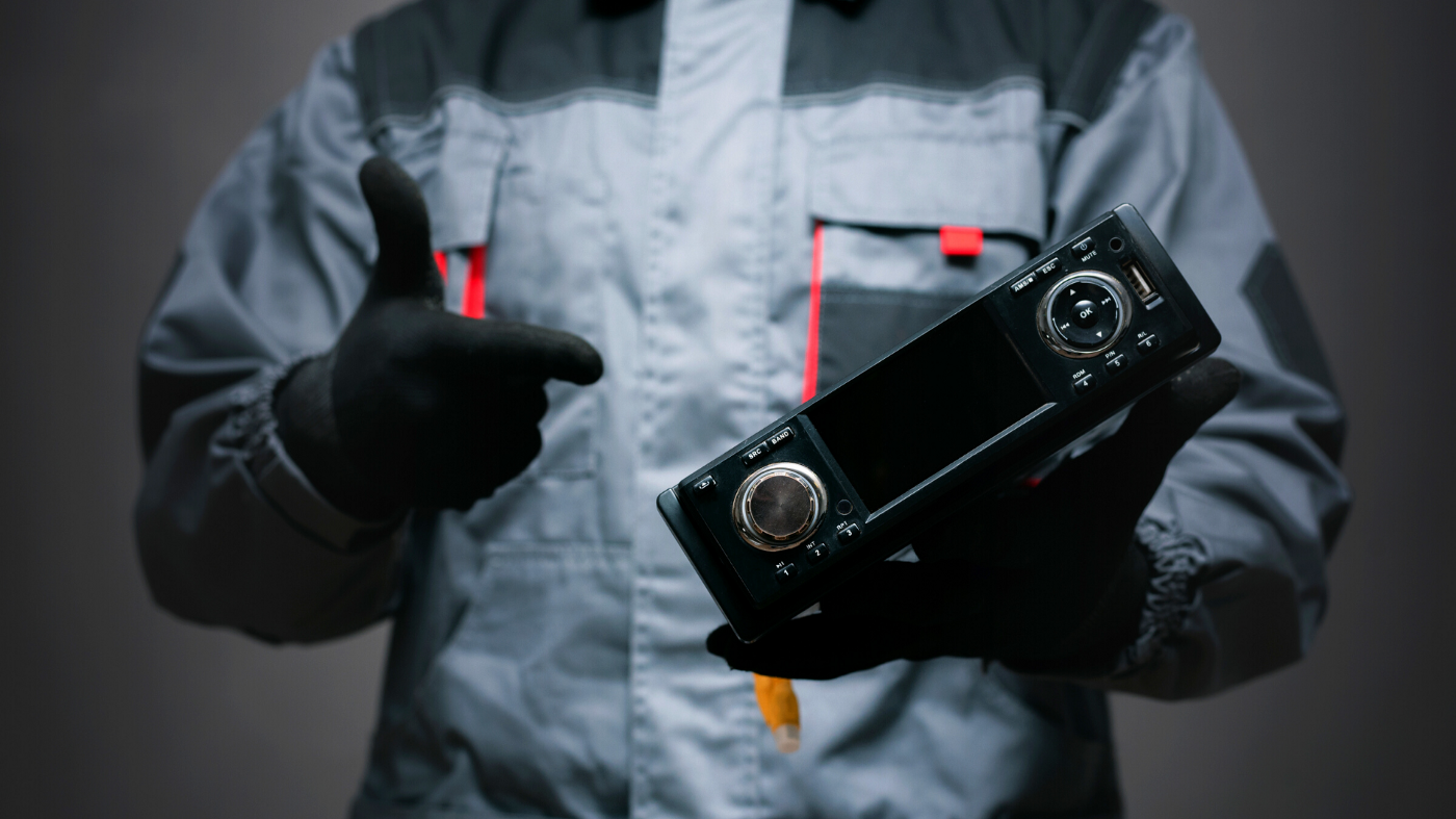 Car radio being held by a man in grey overalls and black gloves