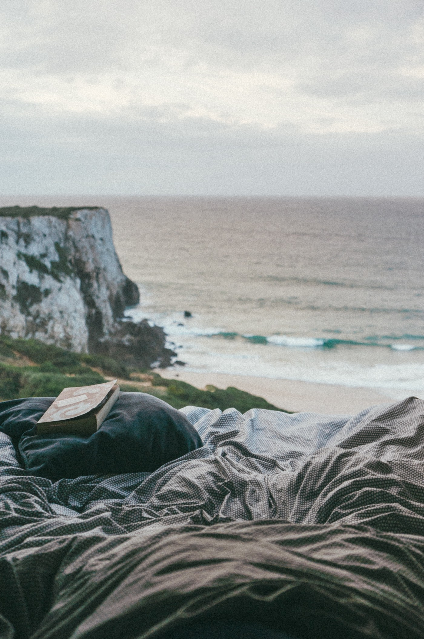 A crumpled with a book on the pillow looking out to a view of the ocean with the cliffs of Dover in the corner.