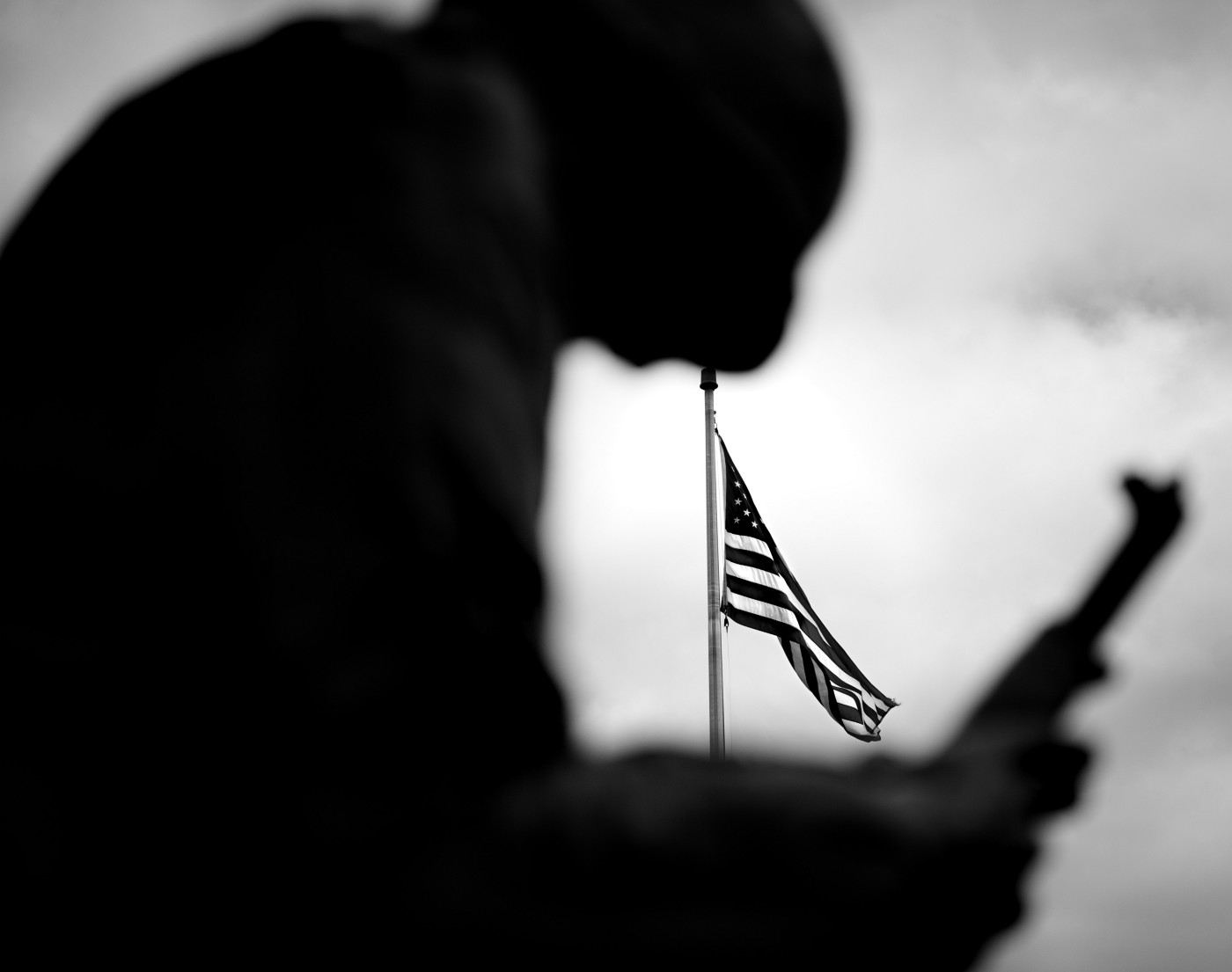 Statue of a solider with the American flag in the background.