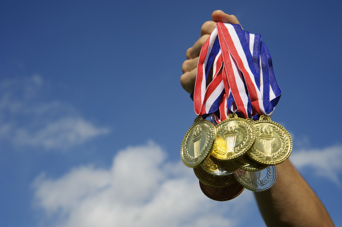 A hand holds up a bunch of gold, silver, and bronze medals against a bright blue sky.