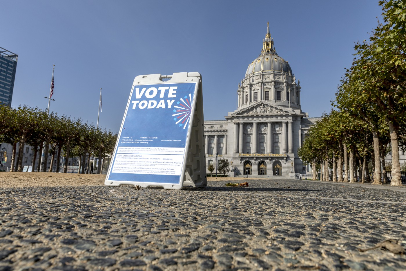 """Low-angle shot of San Francisco City Hall, with a """"vote today"""" sign in the foreground."""