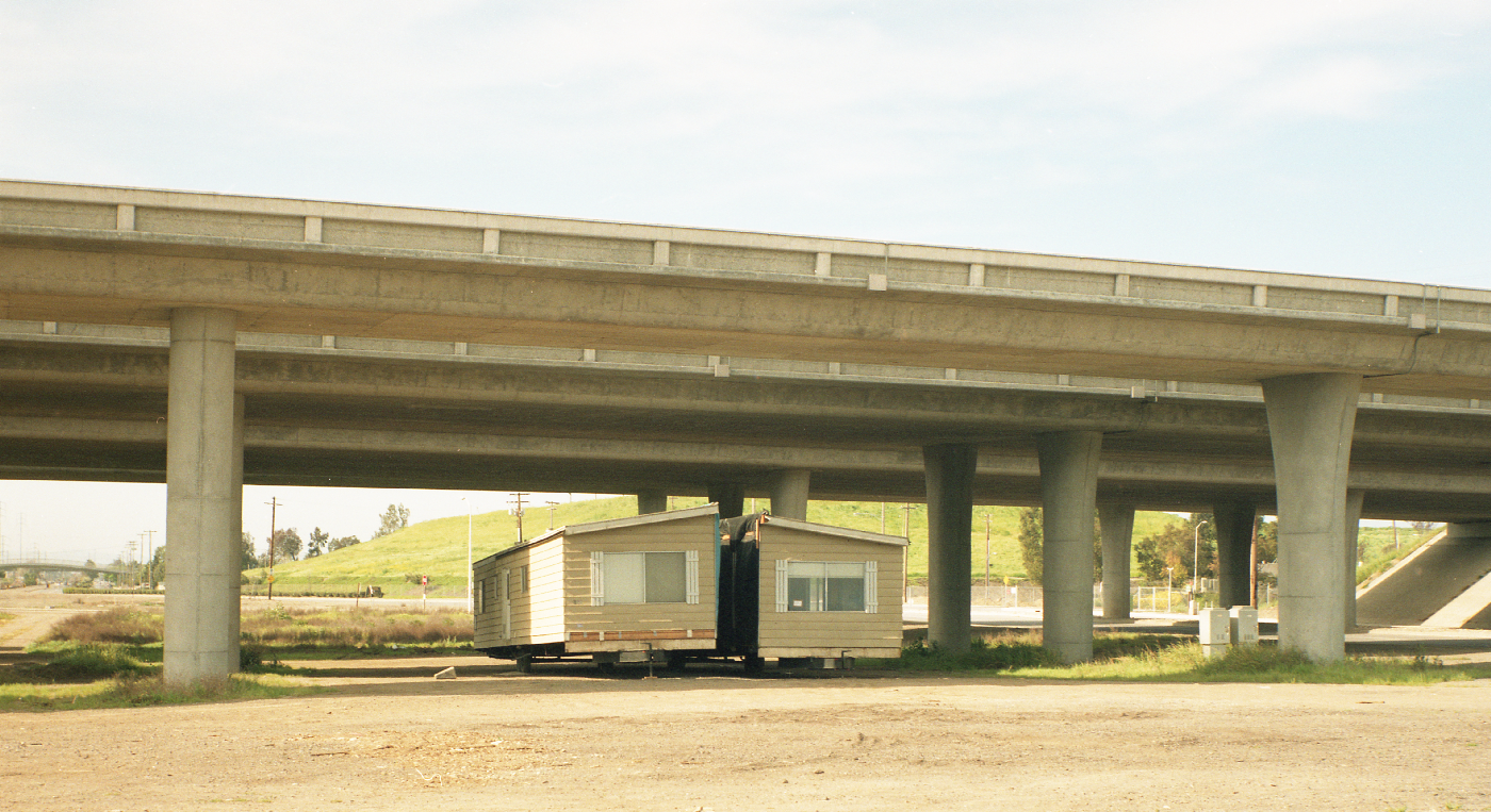 A manufactured home, in two halves, under a freeway overpass