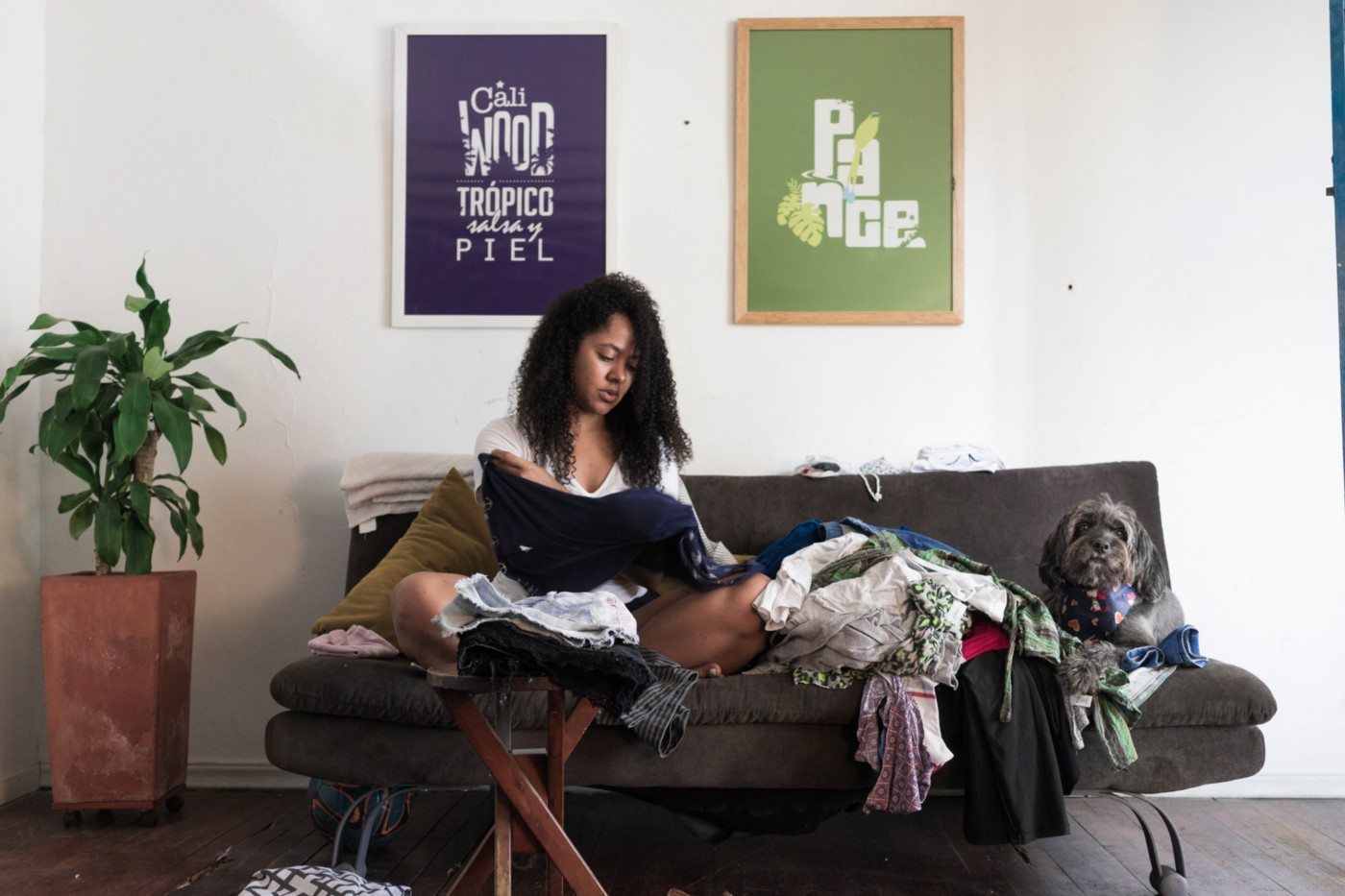 A black woman folds clothes while sitting in her sofa in her living room. There are heaps of clothes.