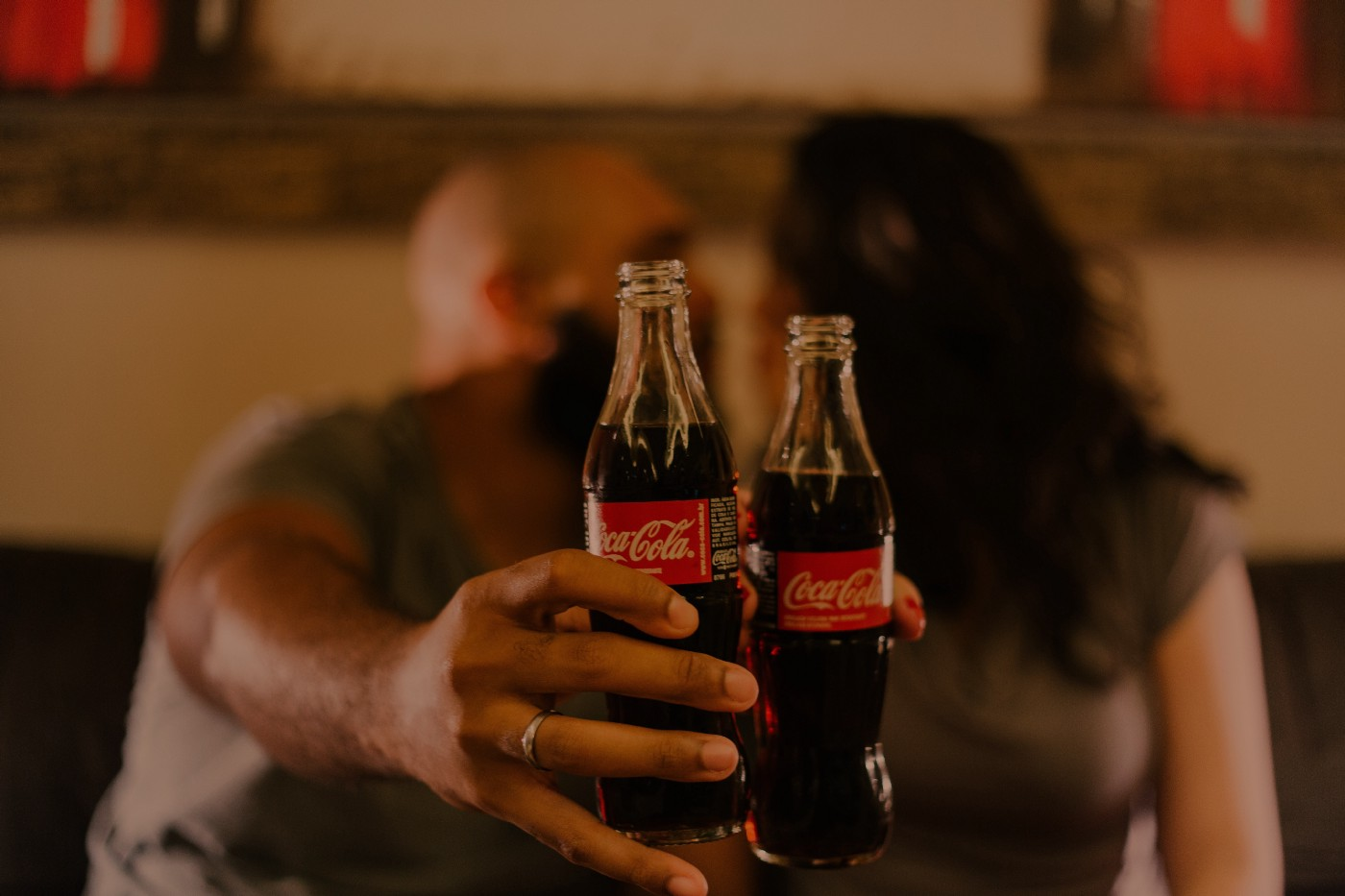 Two people hold up Coca-Cola bottles.