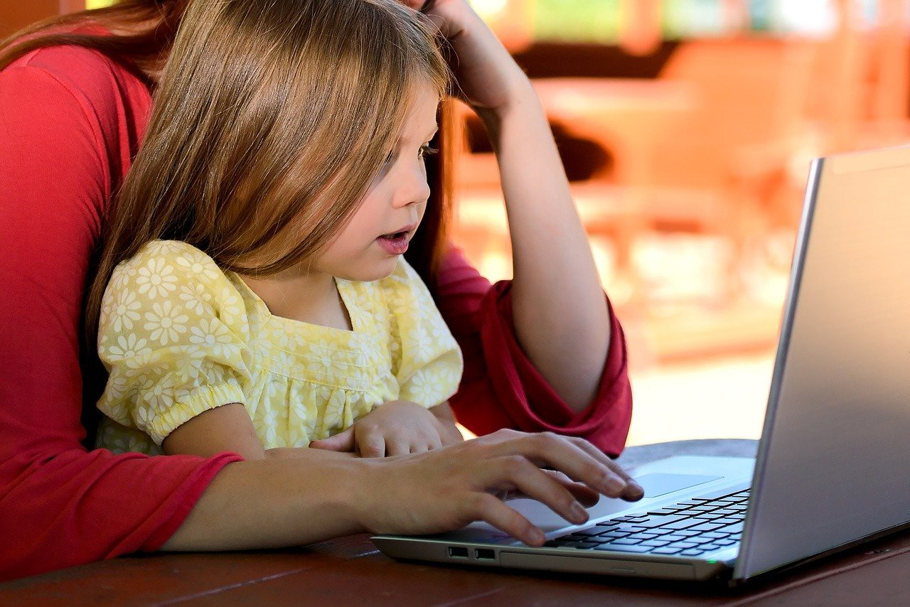 Mom and young daughter both look at laptop.
