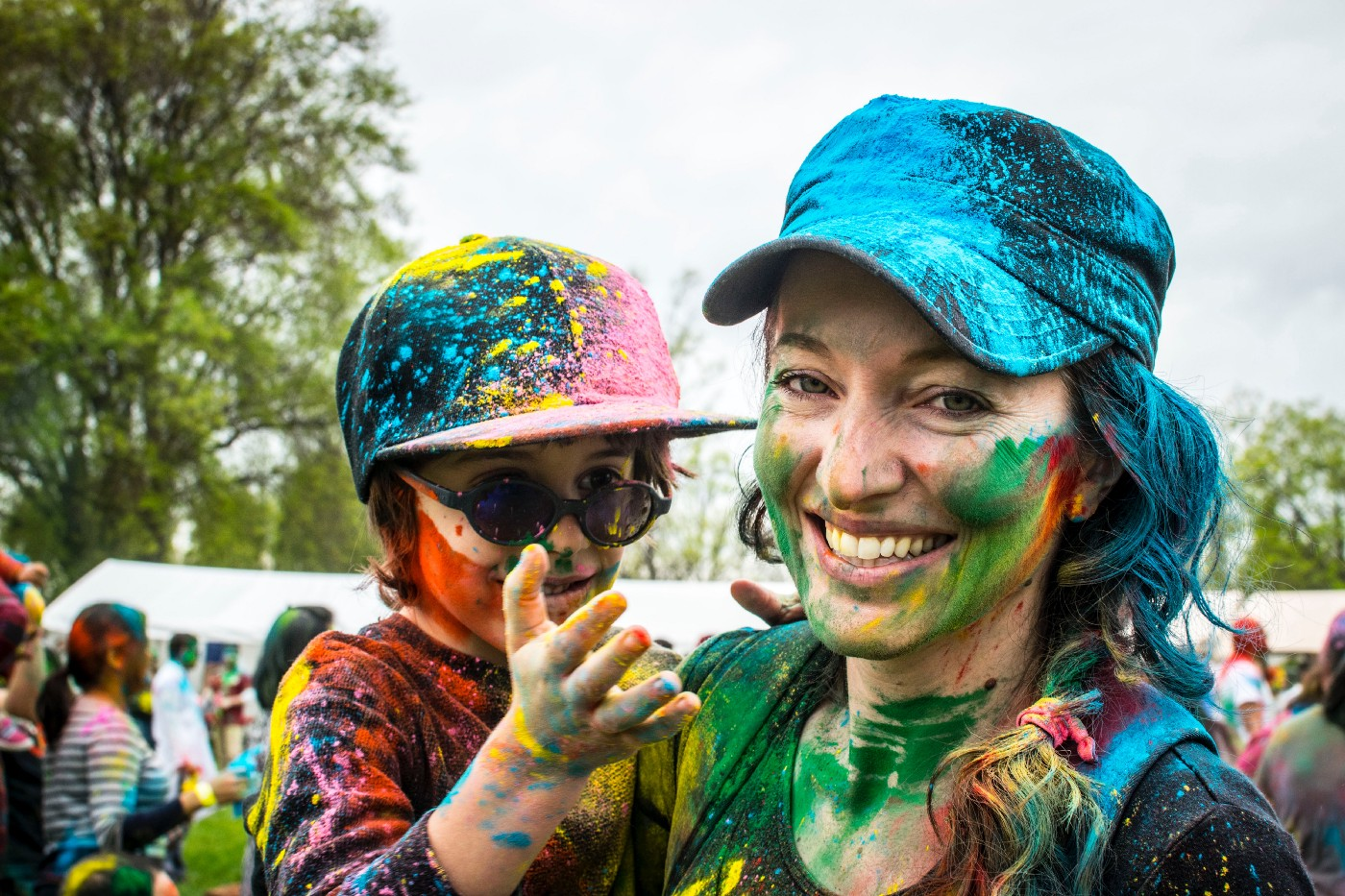 Smiling woman holding boy with outreached hand after both ran through colored paint.