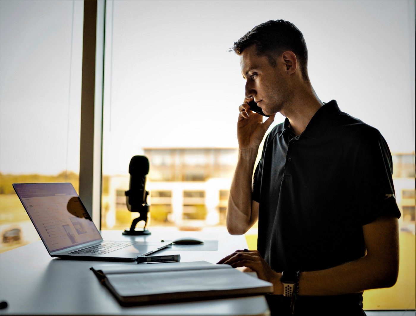 Young man wearing short sleeve black shirt talking on cell phone and sitting at desk with computer and microphone