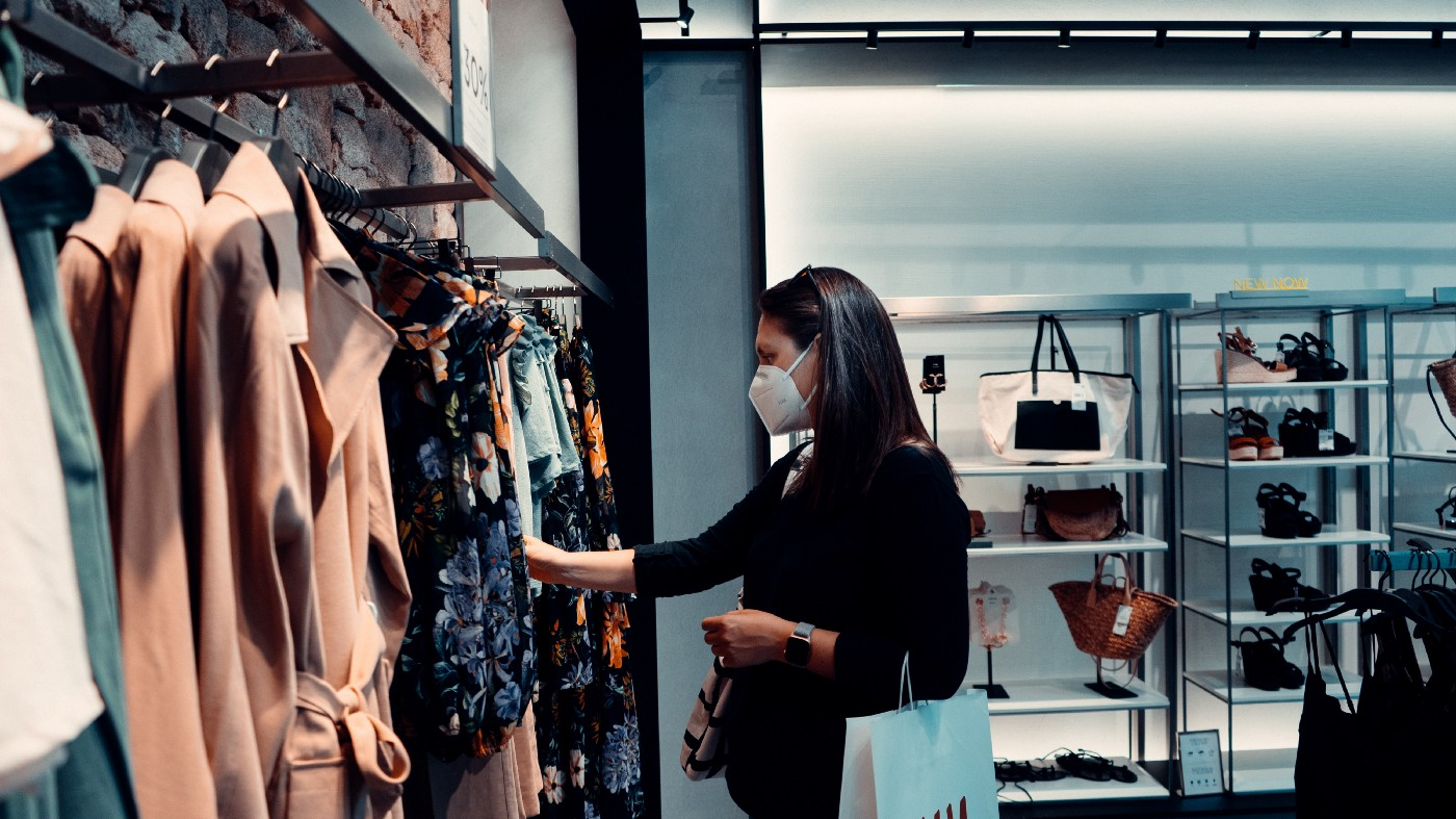A person with long hair, wearing a mask and carrying one shopping bag, flips through clothes at a retail store.