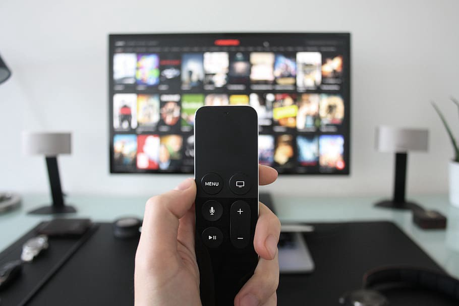 A hand holding a remote with the Netflix screen showing on the TV