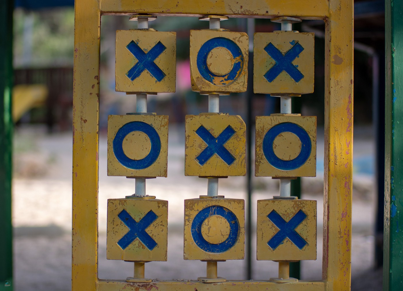 A wooden tic-tac-toe game at a playground.