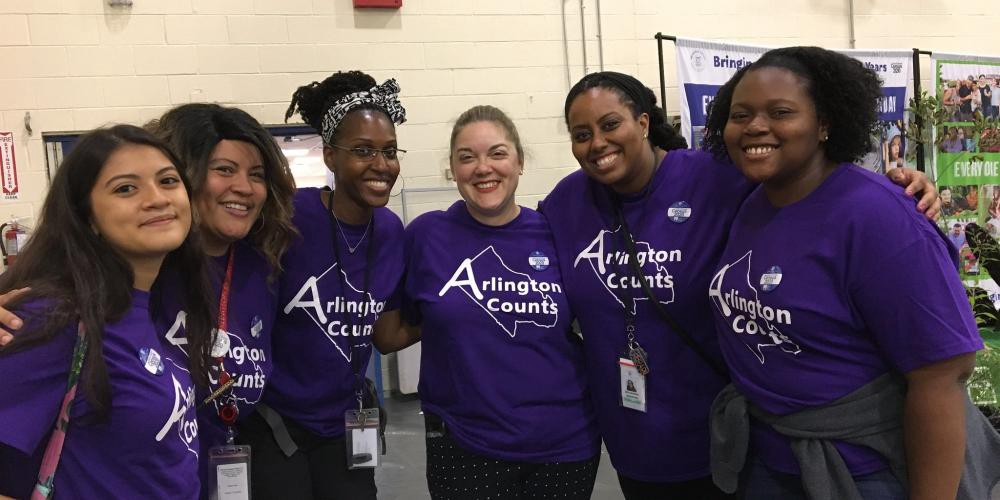 """Five women wearing purple t-shirts that read """"Arlington Counts"""" stand arm-in-arm."""