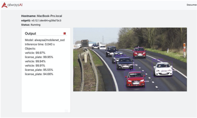 cars on a highway, with object detection boxes around some cars and license plates.
