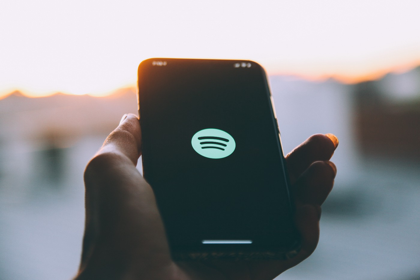 Hand holding a phone with Spotify logo onscreen