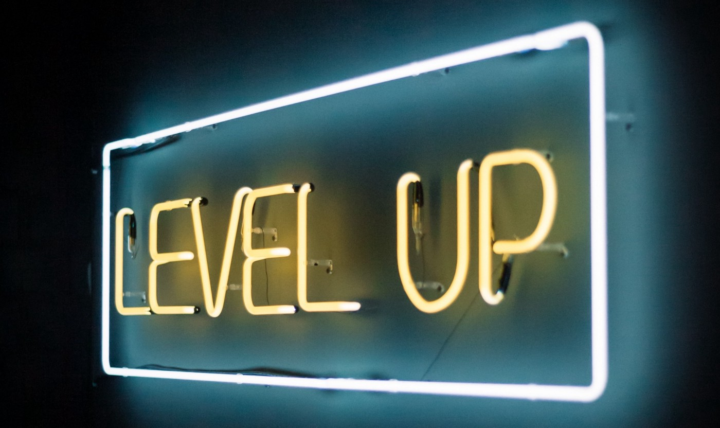 A neon sign saying 'level up' is shown. Level up is written in yellow neon lights
