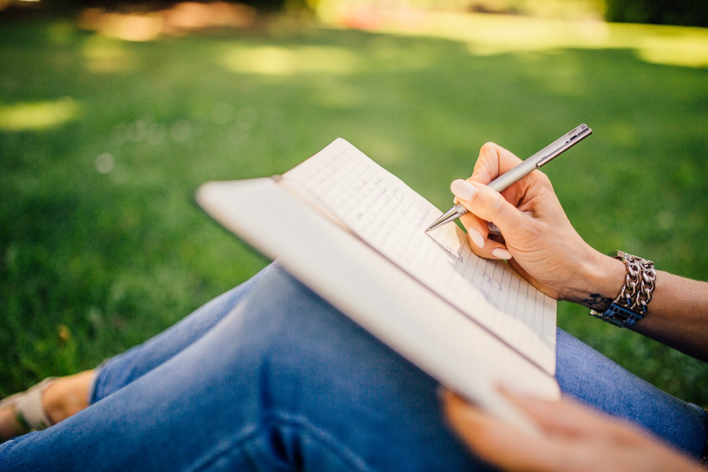 Woman's hand writing in a notebook, sitting on a grass, wearing blue skinny jeans