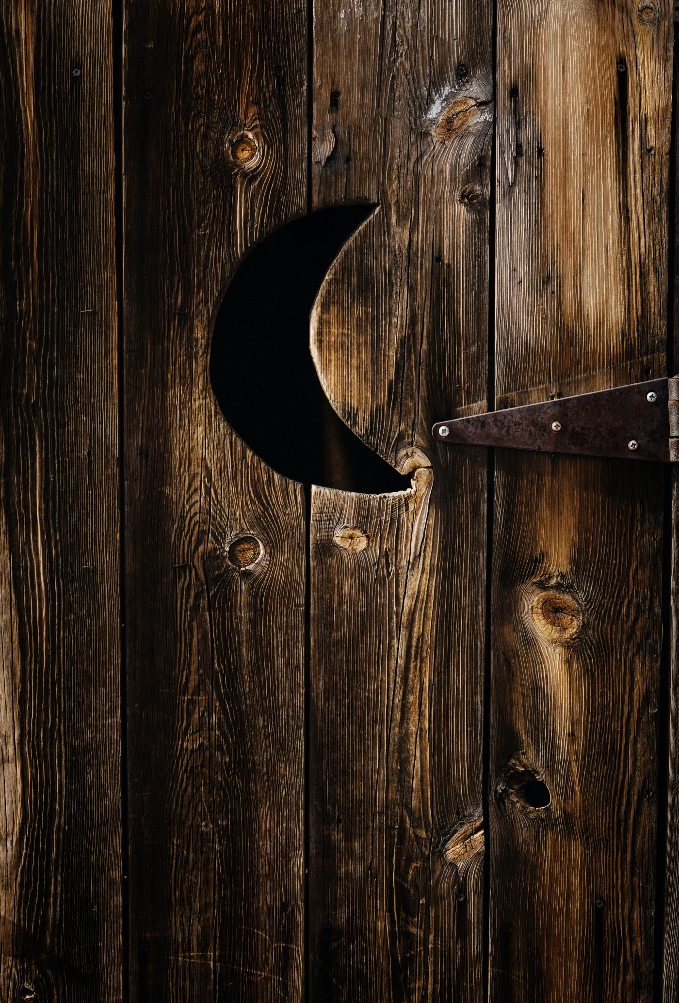 Old American outhouse door with crescent moon cutout