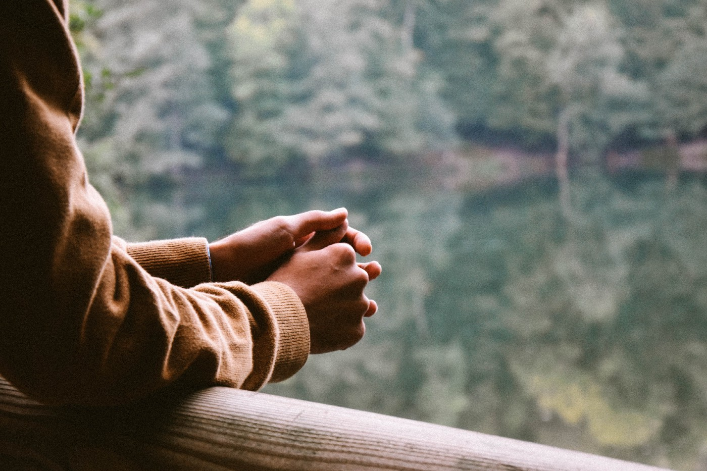 arms held pensively on a rail before a blurred background of trees and a lake