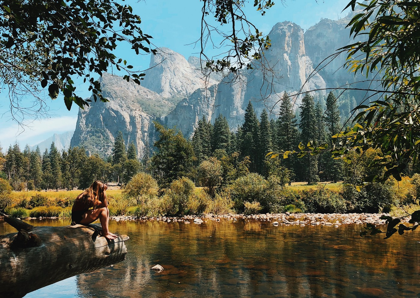 Woman sitting on a tree trunk by the lake in front of picturesque mountains.