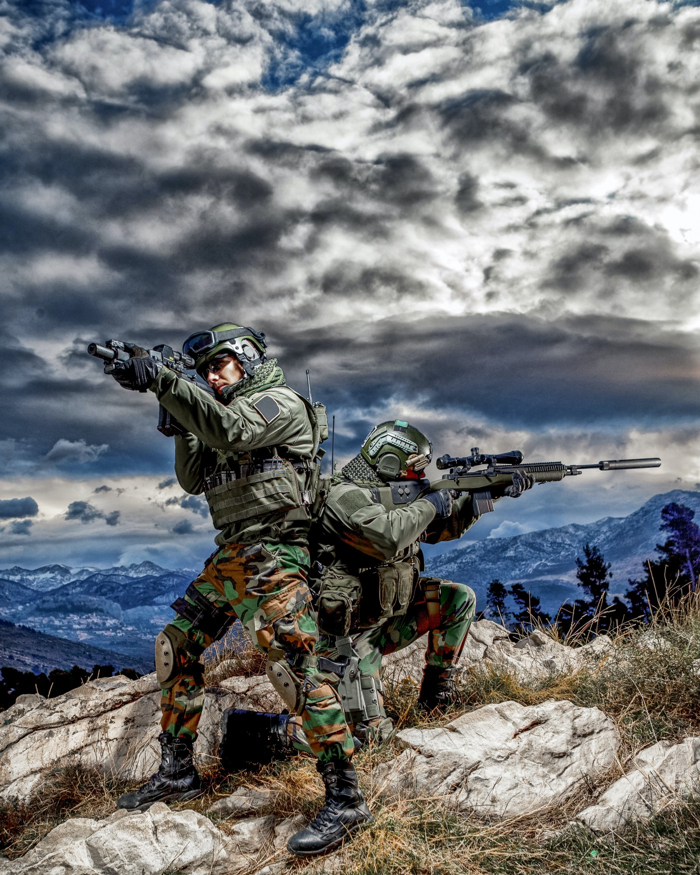 Uniformed soldiers standing back to back on a hilltop with rifles drawn