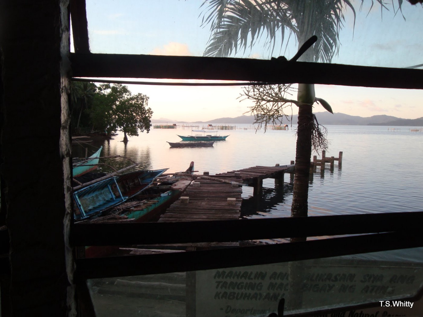 Looking through a window at a ramshackle dock and the sea with small outrigger fishing boats and big bamboo fishing structures scattered around