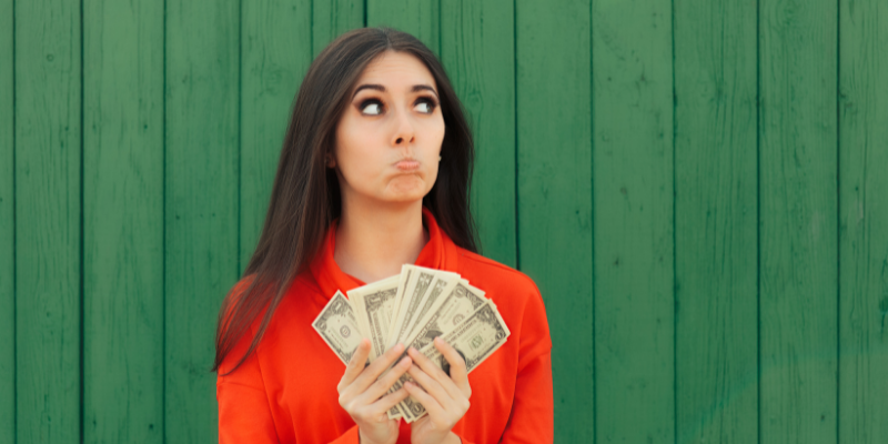 Woman pouting and holding up cash—for my article on How I Use Google Traffic To Make Money With Medium
