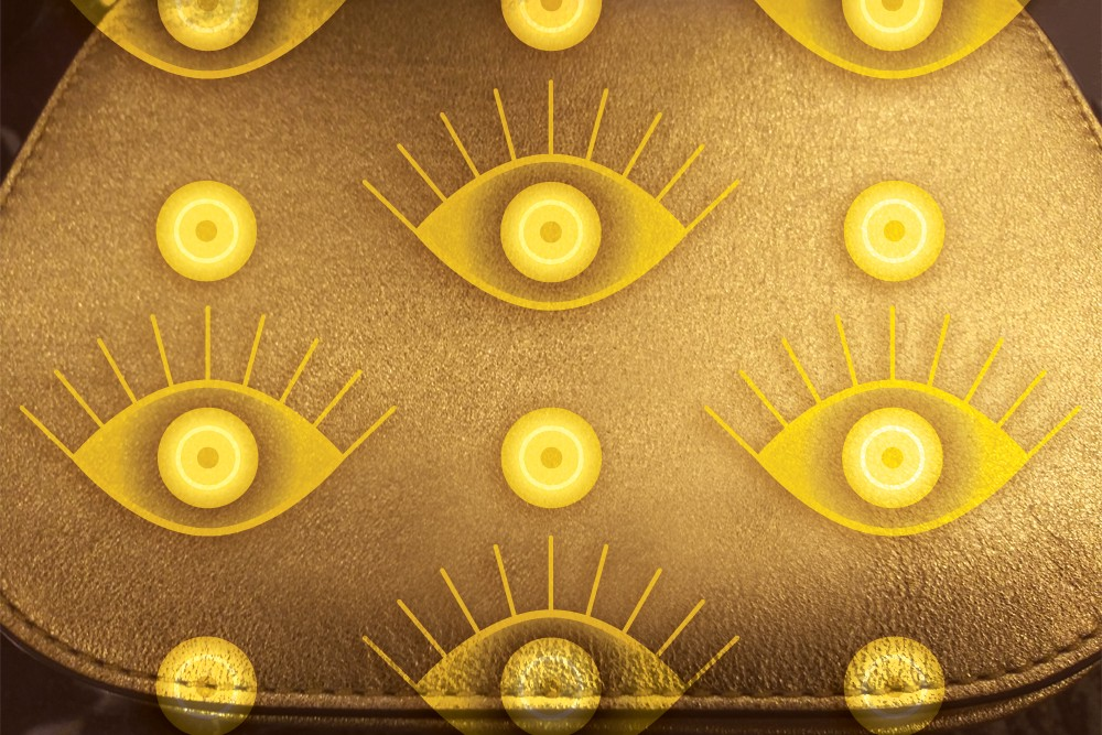 "Simple gold handbag with two styles of bright gold ""evil"" eyes superimposed in a geometric pattern."