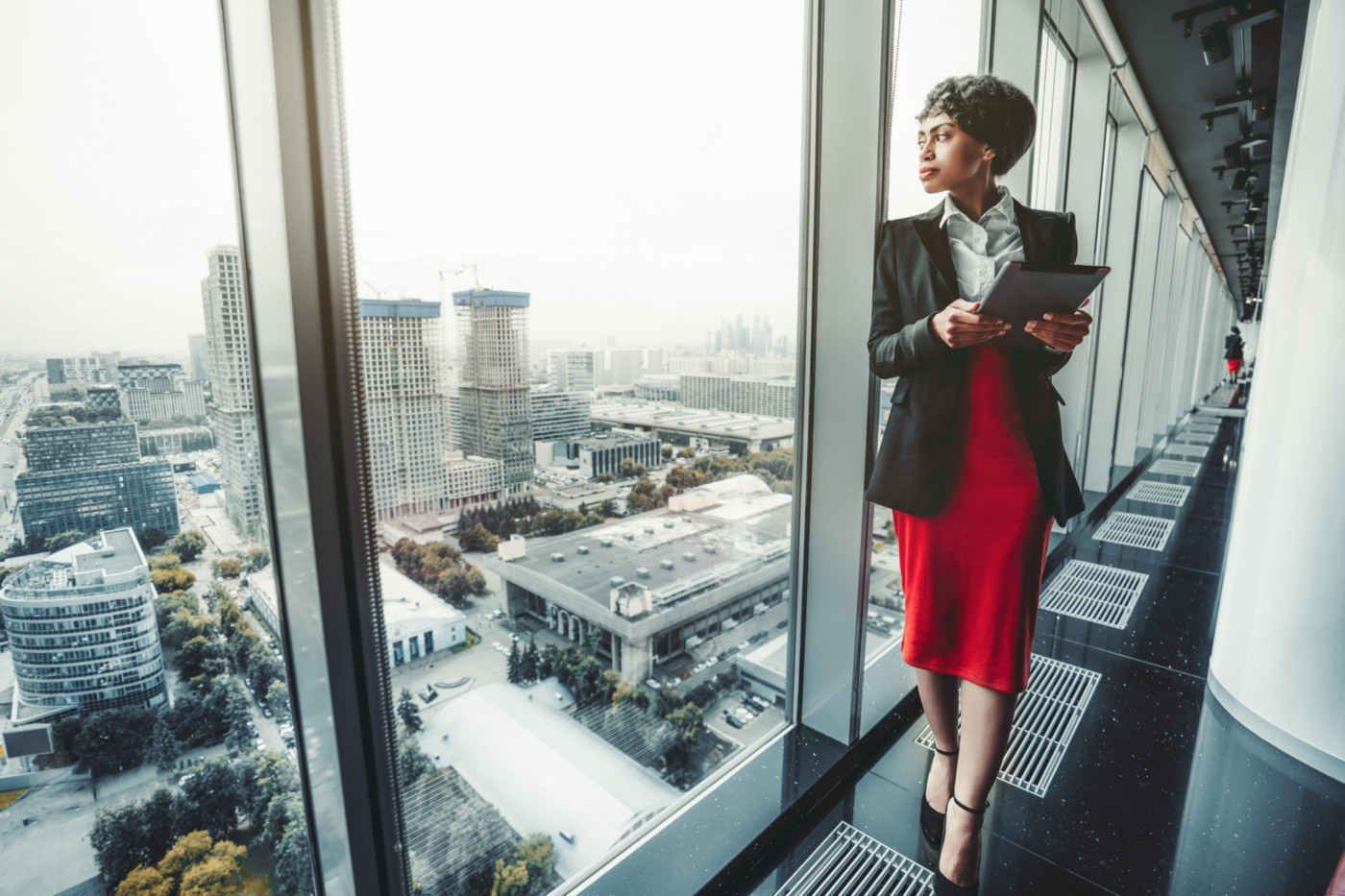A woman looks out of a skyscraper window at the skyline.