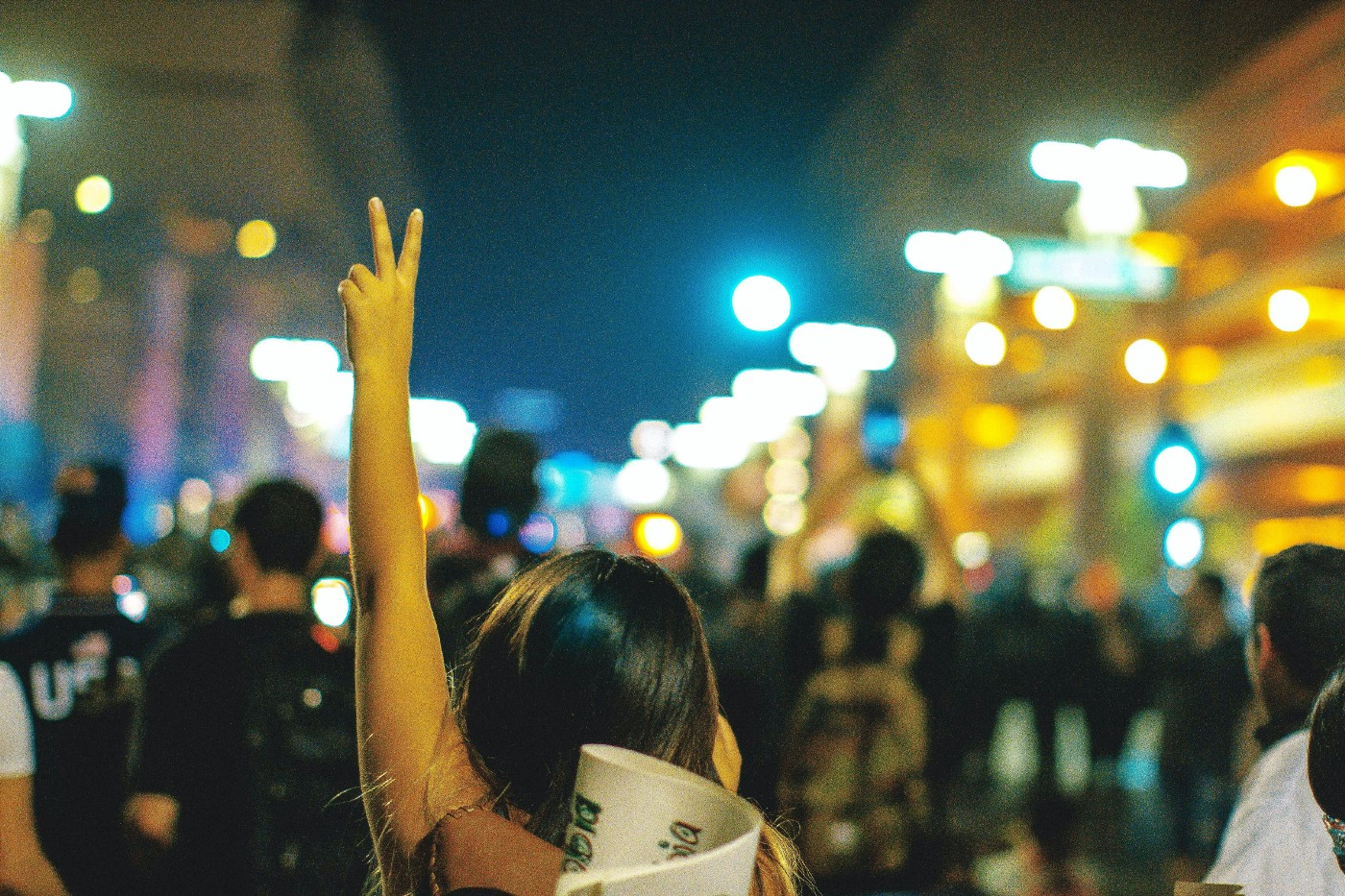 A young woman at the back of a crowd of people showing the peace sign.