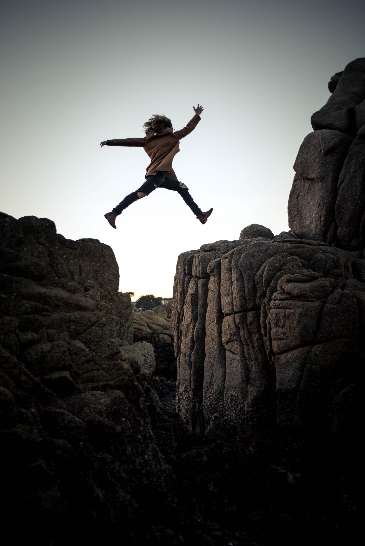 Woman in mid-air jumping between two cliffs