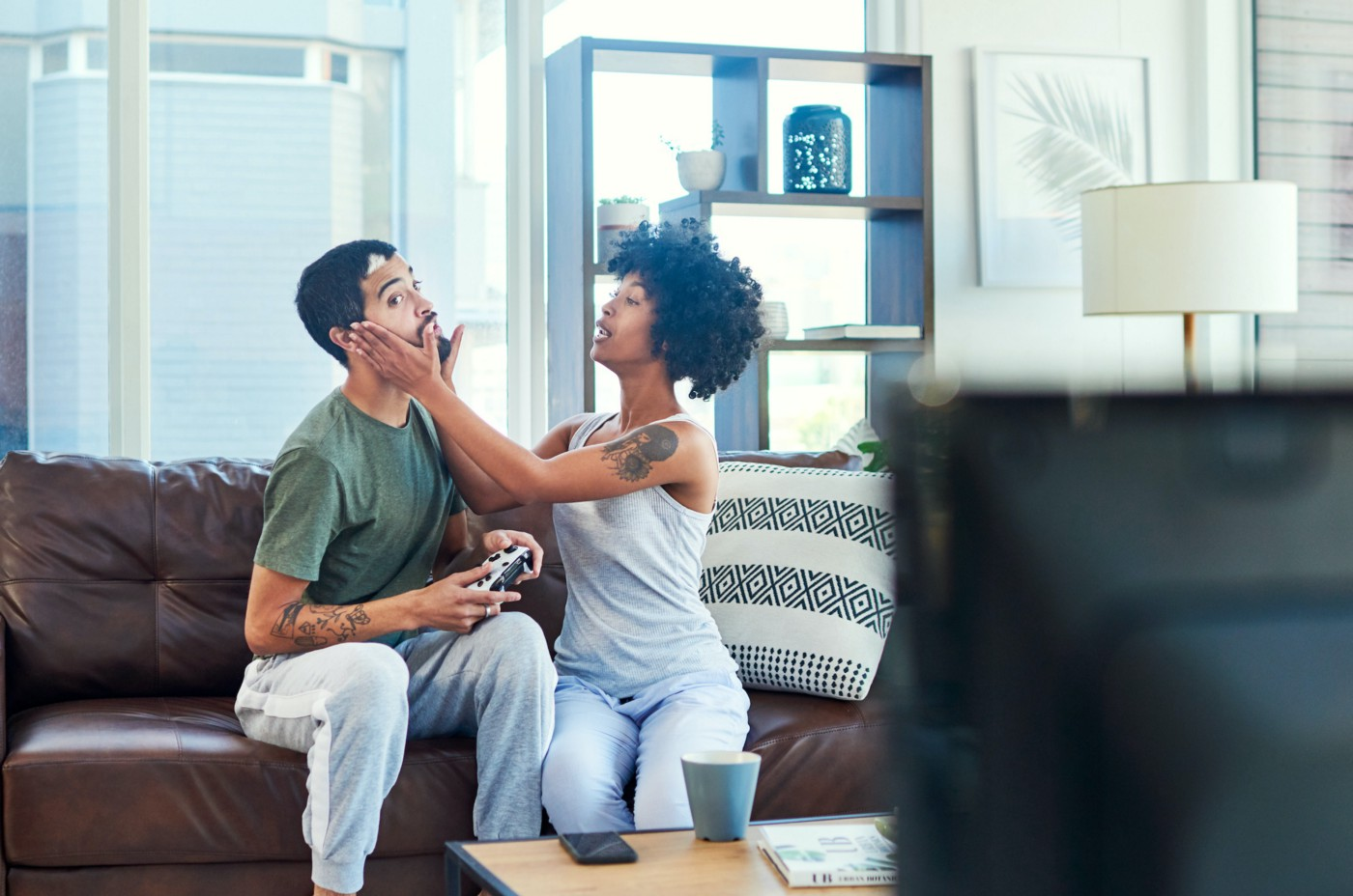 A couple sitting on a couch. One has their hands on the face of the other, who is distracted playing video games.