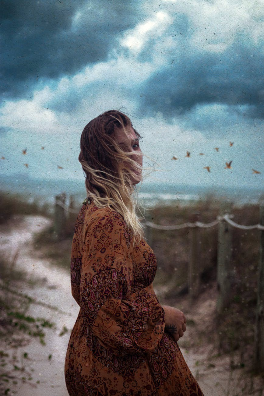 A girl standing along the path, in the background there are many birds in the cloudy sky