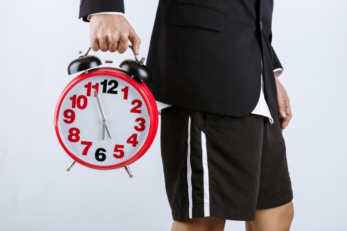 A person wearing a suit jacket and casual shorts holds up a clock.