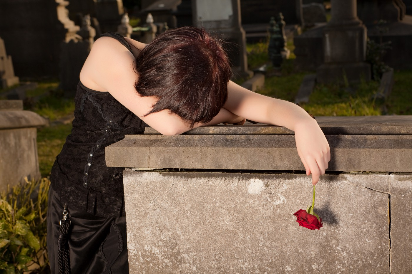 Goth woman with short hair holding a single red rose, sobbing on a grave marker