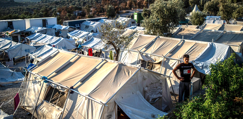 A man standing in front of a series of aid tents set up for refugees spilling out of Camp Moria.