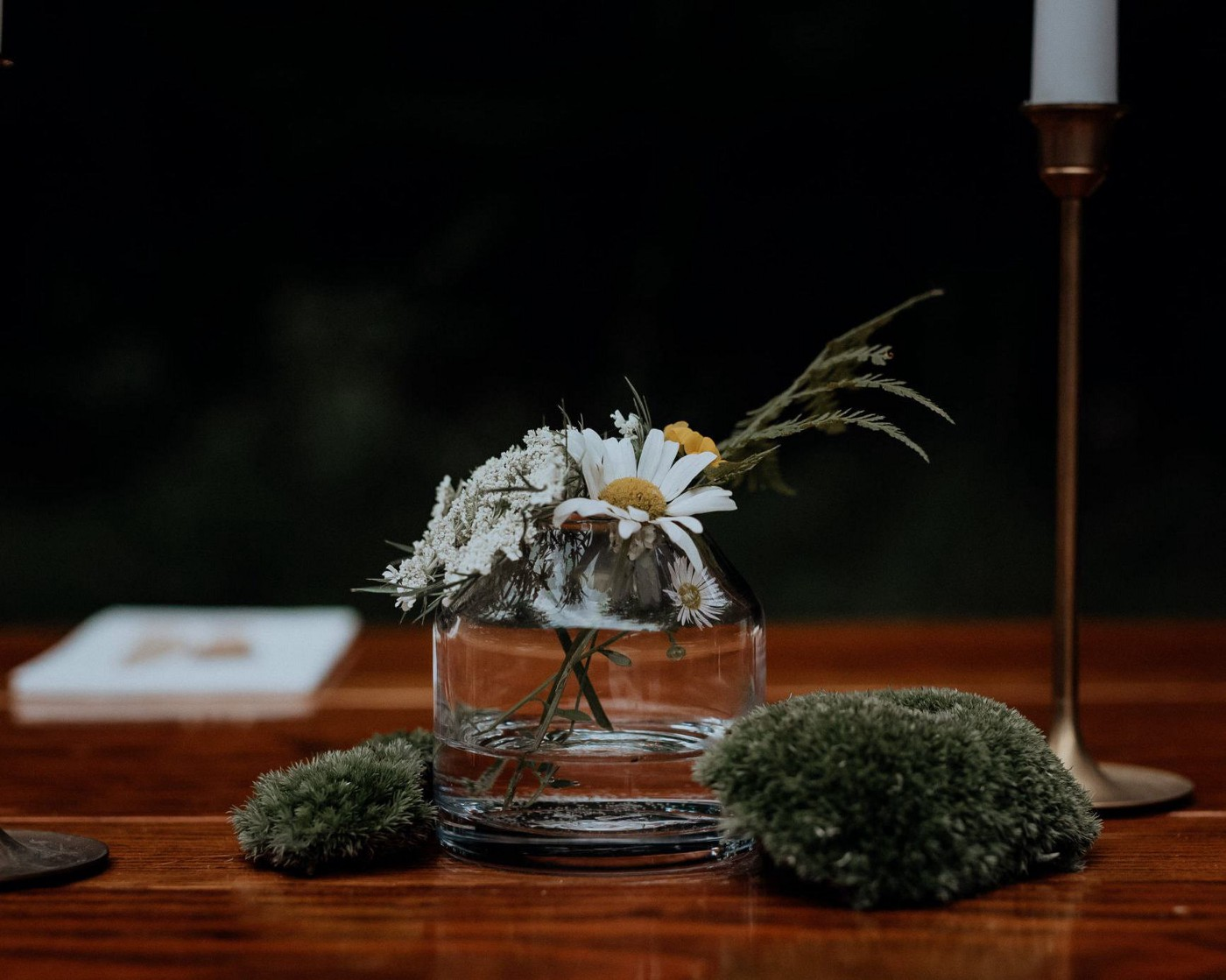 A small wedding centerpiece of foraged flowers and mosses.